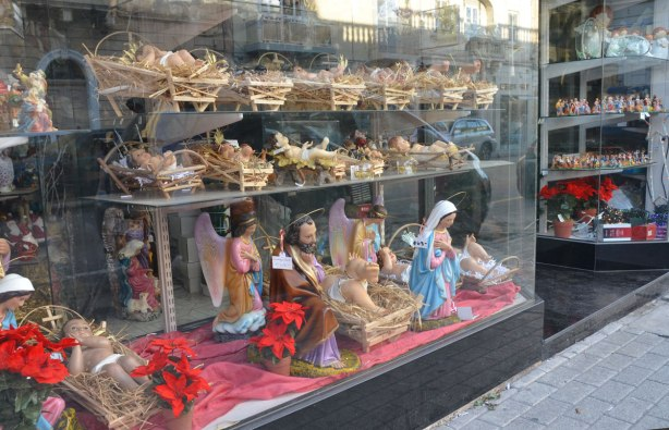 Religious figurines in a shop window.  Most are for Christmas nativity scenes.  There are a lot of baby Jesus's in straw filled wooden managers.