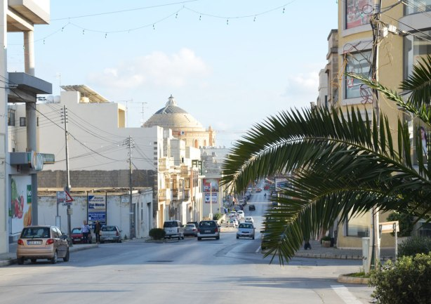 looking down a street, palm tree, buildings, cars, and the dome of a large church at the bottom of the street
