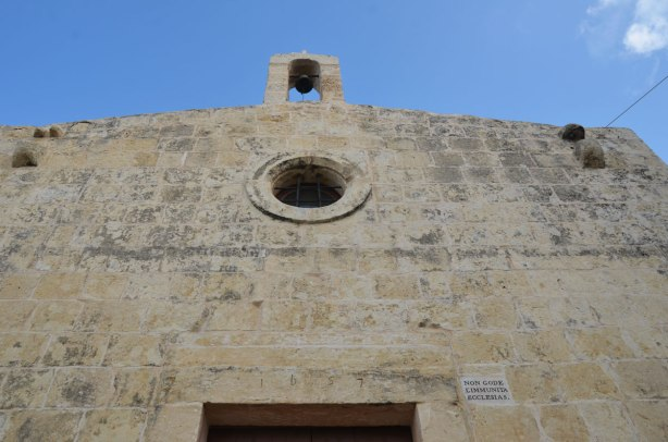 top of the front part of an old church.  It has a  small round window.  The number 1657 is carved into the stone over the doorway.