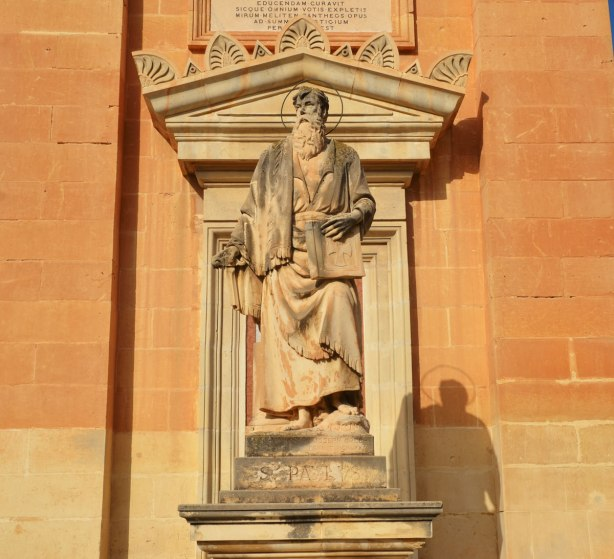 statue of a man holding a book, St. Paul (or St. Paulus) according to the inscription under the statue.  Limestone, on the front of a church in Mosta Malta