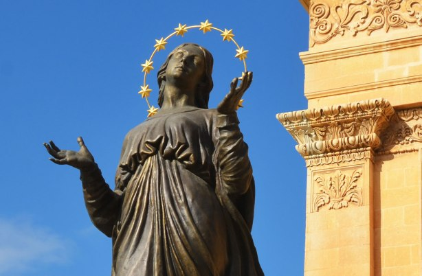 Top part of a bronze statue of the Virgin Mary with her eyes looking towards heaven, and her arms uplifted.  A halo of small gold stars circles her head.  Beside her is the edge of the limestone church.