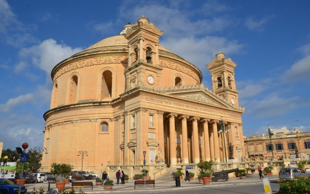 The front of Mosta Rotunda from Pjazza Rotunda, the front of the church with its tall columns can be seen.  The round lower part of the dome is also visible.