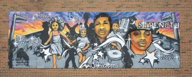 A large mural on a red brick building, painted to celebrate the United Nations Universal Declaration of HUman Rights.  This one includes the words strength, love, respect, unity.  It shows a 5 people engaged in various activities.