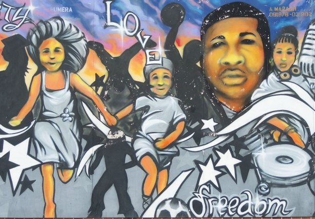 part of a mural showing a boy and girl holding hands as they run.  Also, in the top right corner is a black man with a microphone.   The words 'love' and 'freedom' are also written on the mural.