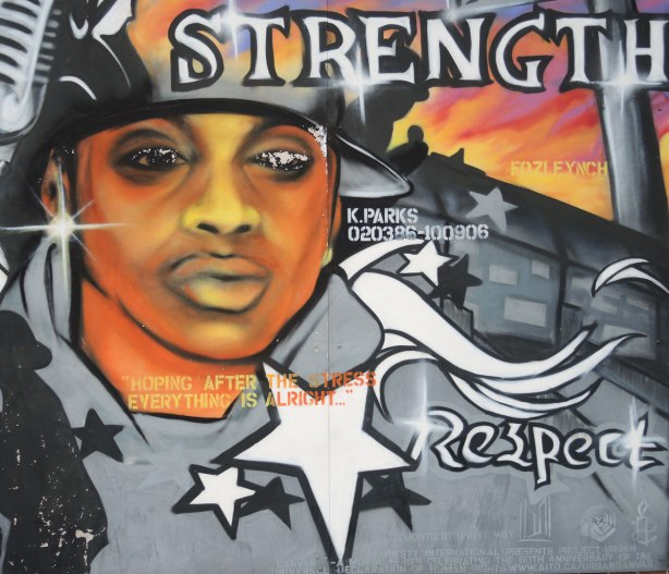 "Part of a mural showing a black man's face.  The words strength and respect are written there.  Also 4 white stars, and the words ""hoping after the stress everything is okay."""