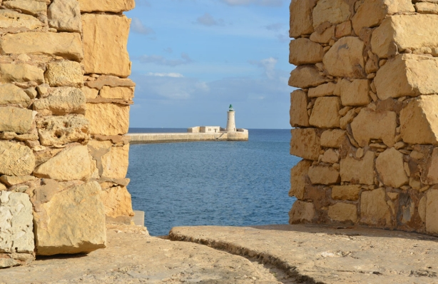 Looking through a gap in the bastions towards the lighthouse that is at the end of a pier