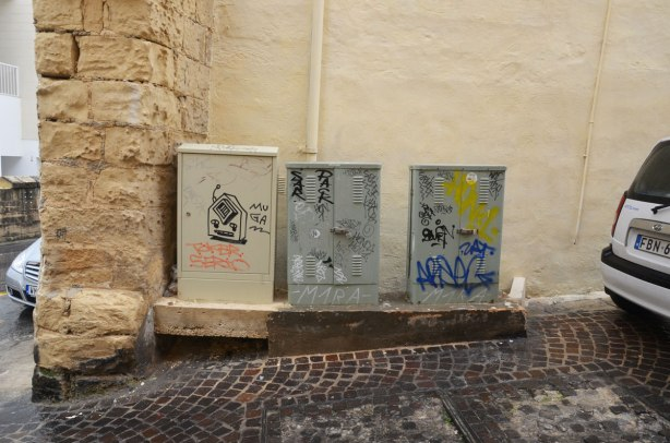 Three electrical boxes in a row, beside a cobblestone street.  They have graffiti on them.