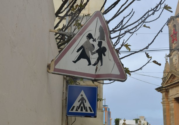 Crossing sign, triangular with red border, of two people holding hands