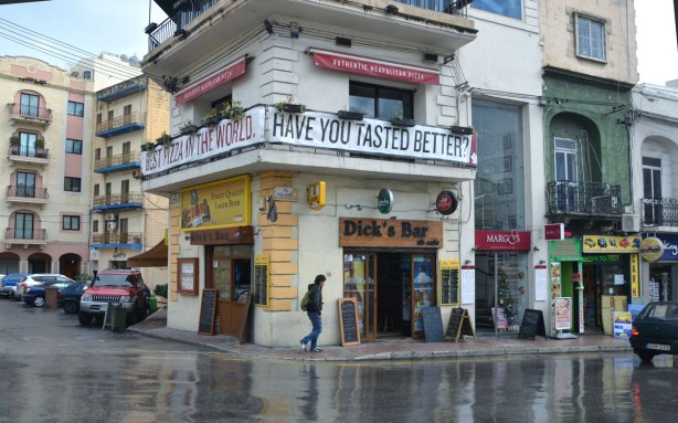 Looking across the street to an intersection, the streets are wet.  Dicks Bar is on the corner, a two storey white building with a balcony running around it.  There is a large banner hanging from the balcony that says 'Have you tasted better'