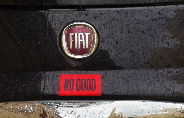 The back part of a black Fiat 500 on which someone has added a red sticker that says NO GOOD
