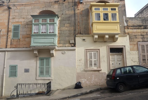 looking across the street to two houses, each with a wooden balcony structure overlooking the street.  One is pale green and the other is yellow.