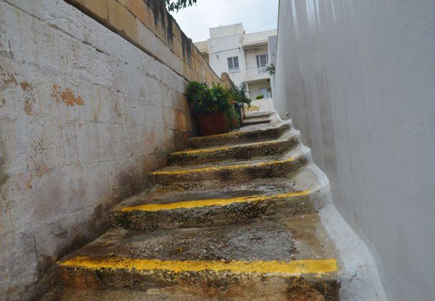 A narrow set of stairs between two buildings.  The edges of the steps are painted yellow.  There are a couple of pots of plants near the top of the steps.