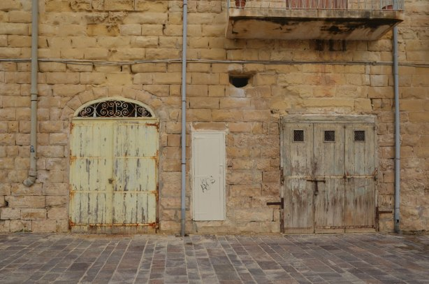 Old wooden shutters on doors of an old limestone building.
