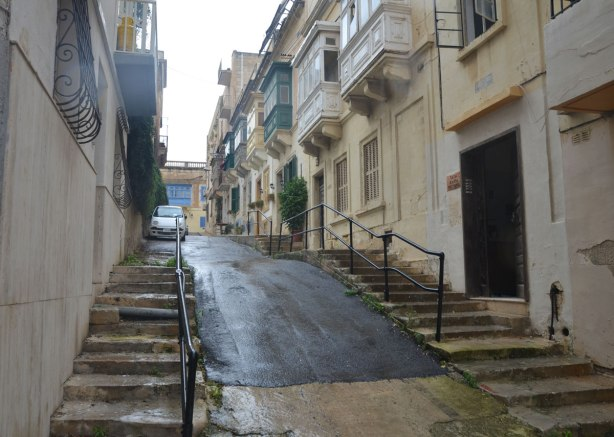A narrow steep street with stairs on either side.  A white car is parked at the top of the hill.