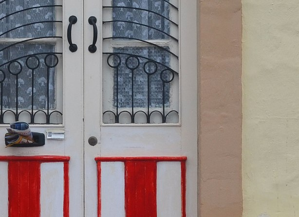 close up of a door.  The lower part is painted in red and white stripes.  The upper part has two glass panels that are covered in interesting metal bars that are curved and circular