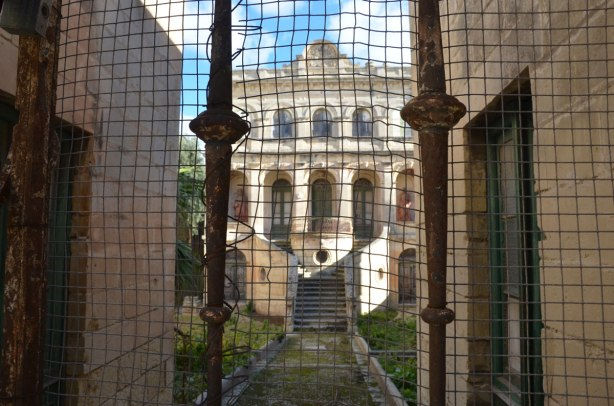 an old, large, ornate, 3 storey abandoned stone house in Rabat, behind an old rusty wire mesh gate.