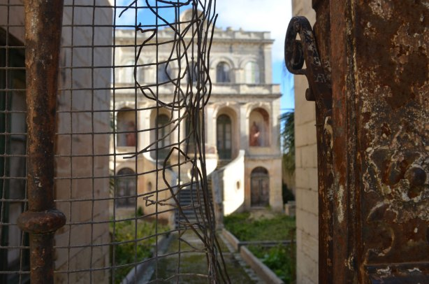 an old, large, ornate, 3 storey abandoned stone house in Rabat, behind an old rusty wire mesh gate with a rip in it.