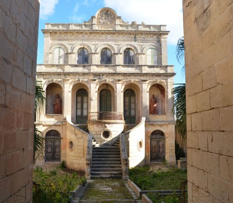 an old, large, ornate, 3 storey abandoned stone house in Rabat with grass growing over the stone path to the entrance