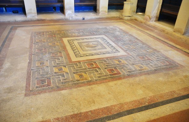 Romasn mosaic floor made of many small tiles, geometric pattern around a center square that is a picture of two birds in a bowl