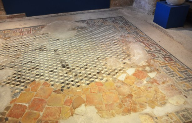 Roman mosiac floor in various states of repair.  Some smaller tiles and some medium sized tiles.