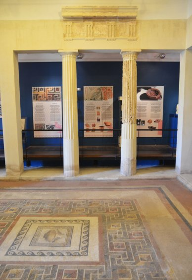 mosiac floor in a Roman house museum.  Part of the columns and stone work over the columns has been restored to show what it would have looked like in Roman times.