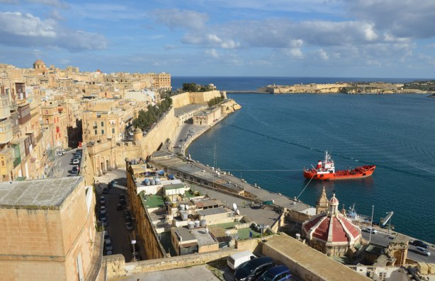 shoreline of Valletta, with blue water, limestone walls, limestone buildings and a blue sky.