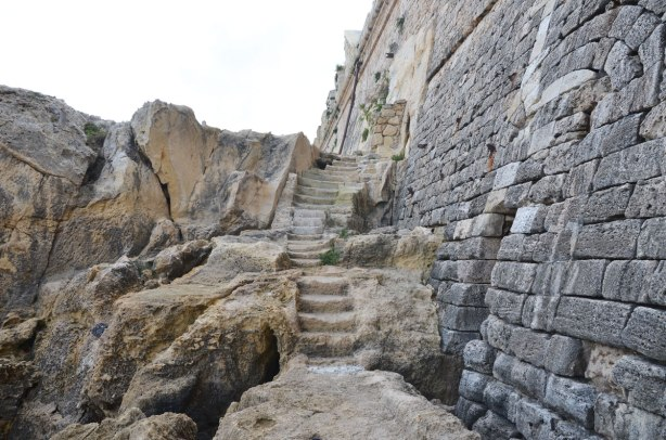 Steps carved into the rocks at the base of a stone wall.