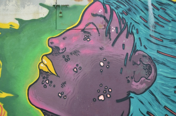 Street art painting of a large purple face in profile.  Yellow lips, blue hair.