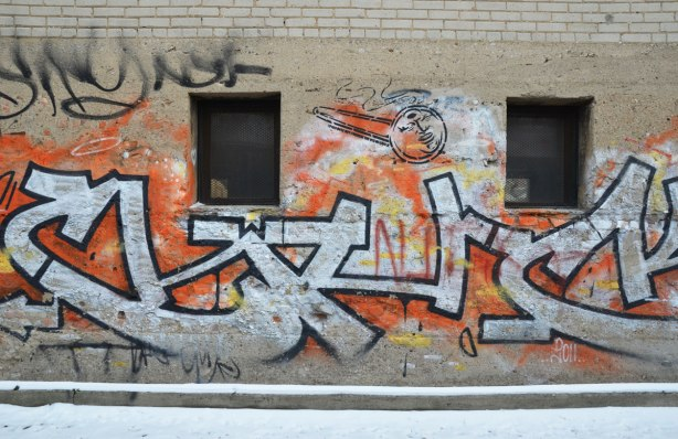 "tags on a brick wall in black, orange and white.  Anti Rob Ford graffiti also there in the form of a crack pipe with Fords face on it.  ""Spud doesn't condone crack""  I think are the words written beside the crack pipe."