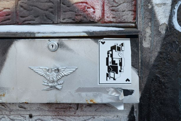 a small black and white lovebot sticker, the one that looks like a king of hearts playing card, is on the mailbox