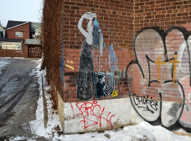 Wheatpaste paste up picture of a woman in a long black sleeveless dress who is pouring water from a jug over the back of her head.   The water is falling on a girl who is sitting behind the woman.  The girl is holding an umbrella.