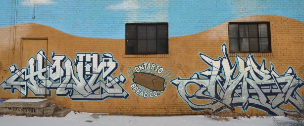street art on a wall.  In the middle is a brown loaf of bread with the words Ontario Bread Co written around it.  There is a black and white tag on either side.  two windows and a door of the building are also in the photo.