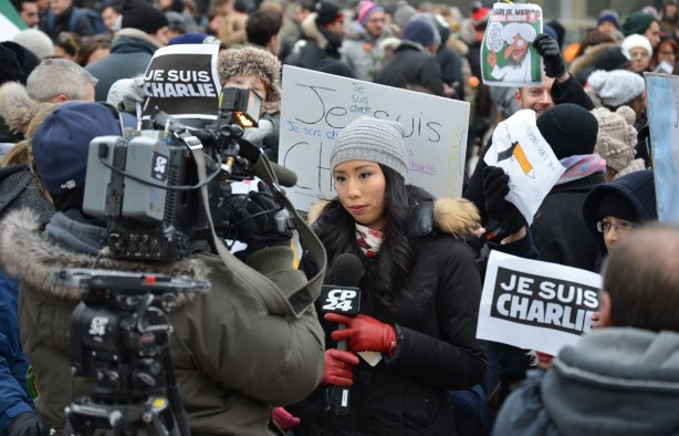 A large TV camera is filming a reporter from CP24.  People behind the reporter are holding Je Suis Charlie signs.