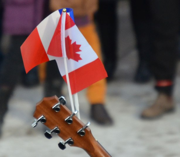 Close up photo of two small flags, one Canadian and the other French, on the end of a guitar.