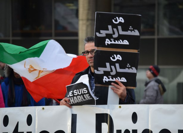 A man is holding three signs.  One says 'Je Suis Charlie' and two are in arabic.  He standing behind a large white sign withblack letters.  The words can't be read in this photo.  An Iranian flag is being held by someone standing behind him.