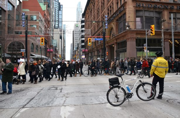People are walking through the intersection of Queen and Yonge streets as they march in the Je Suis Charlie rally.  A policeman in a yellow jacket is standing in the intersection to help prevent the cars from interfering.