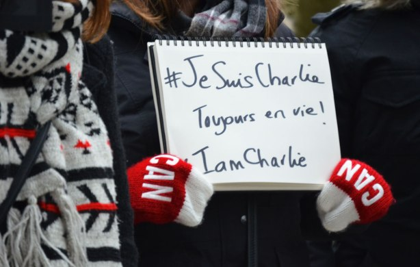 Close up of a sign that says 'Je suis Charlie Toujours en vie!  I am Charlie' in black letters on white paper.  The sign is being held by someone who is wearing red mitts with big CAN on them in white.