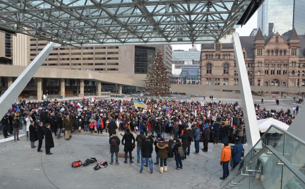A crowd in front of the stage at Nathan Phillips square on a January day when the Christmas tree in front of City Hall is still there.