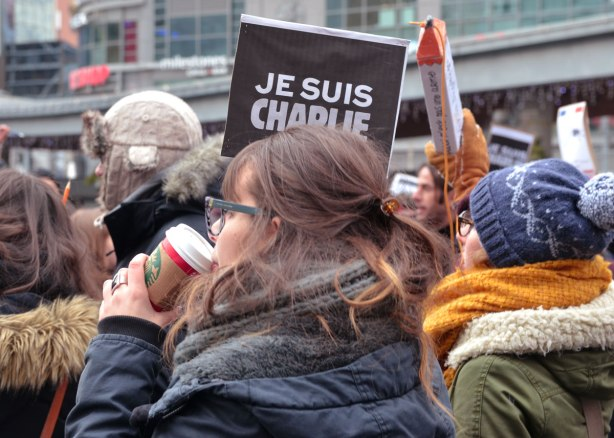 Two women.  One is holding a Je Suis Charlie sign in one hand and a Starbucks cup in the other.  THe other woman has a large pencil shaped sign.