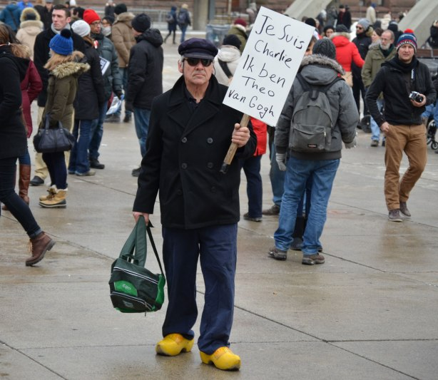 A man is wearing yellow clogs and holding a sign that says Je Suis CHarlie. Ik ben Theo Van Gogh