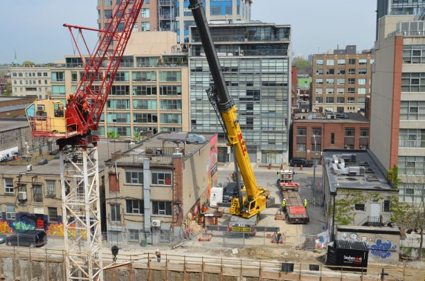 Men on a crane working above a hole in the ground where a new condo is being built.