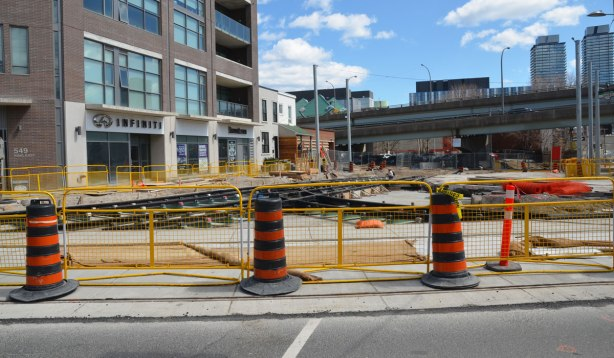 Black and orange traffic cones along with a yellow fence block traffic from entering a construction site at an intersection where new street car tracks are being laid.