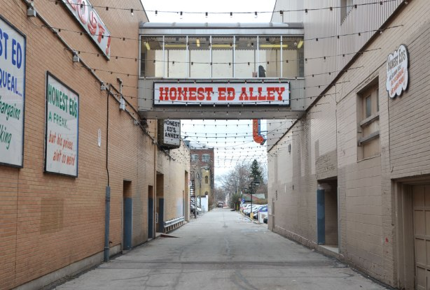 Standing on Bloor street looking south through the alley beside Honest Eds store.  There is a glass covered walkway between the buildings on either side of the alley.  On the side of the wwalkway is a sign that syas 'Honest Ed Alley'.  The alley leads to a parking lot.