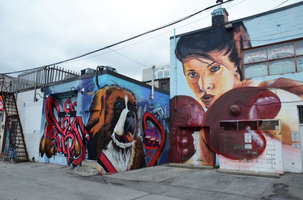 large mural of a woman with boxing gloves on.   Beside her is a picture of a large dog's face.