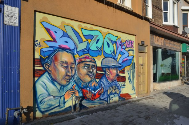 Street art mural by elicser of three men on a bench.  One is smoking a cigarette, one is reading and one is holding a lunch box in his hands.