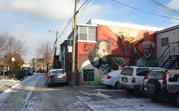 laneway in winter, some snow and ice on the ground.  Three cars parked.  A mural on the side of a two storey building.  Reddish rust coloured background with two faces, one woman and one man.