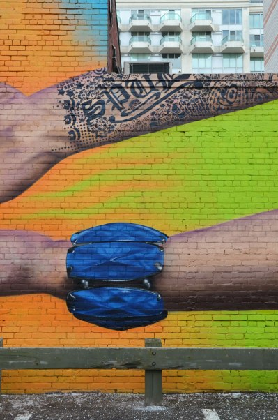 Part of a mural showing wrists of two arms.  The upper arm is tattooed in black ink and the tattoo includes the word SPUD..  The bottom wrist is wearing a large blue bracelet.  The background is bright green and orange.