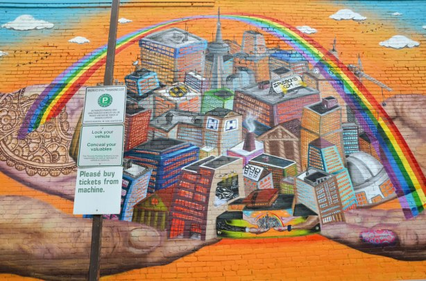 Center part of mural showing a city in 3D under a rainbow, on an orange background, and being held up by four large hands.