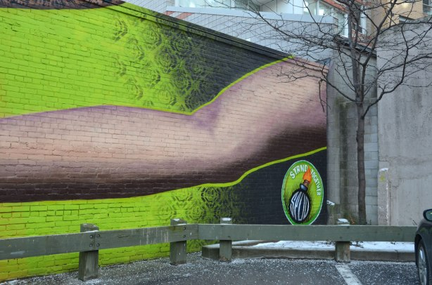 Far right side of mural, behind a low fence, bright green background with a long arm reaching across the photo.  A small tree stands in the corner of the parking lot, on the far right of this picture.  An apartment building is behind.  Spud bomb logo in the bottom right,