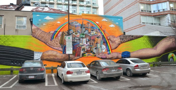 Stand Together mural on Richmond Street, it is the back of a building as well as the back wall of a parking lot.  Four cars are parked in front of the mural which is 4 large arms and hands.  Together the hands are holding a city that is under a rainbow.